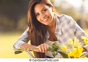 beautiful young woman with flowers on a bike