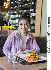 beautiful young woman with food in restaurant