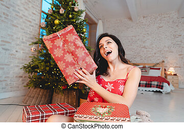 Beautiful young woman with gifts on the background of the Christmas tree