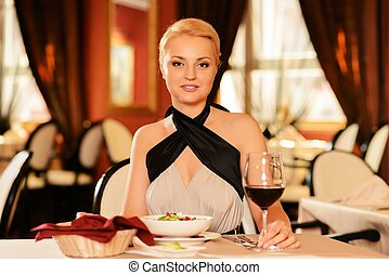 Beautiful young woman with glass of red wine in restaurant
