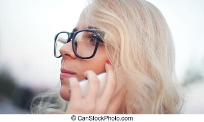 Beautiful young woman with glasses is talking on the phone
