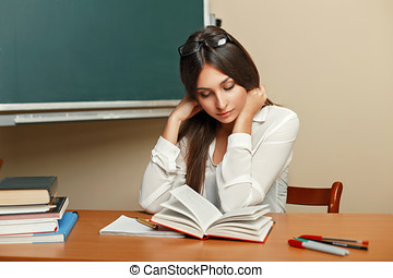 Beautiful young woman with glasses reading a book in the classroom.