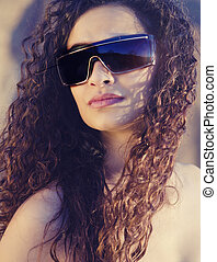 Beautiful young woman with gorgeous curly hair wearing sunglasses