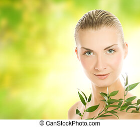 Beautiful young woman with green plant over abstract blurred background