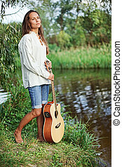 Beautiful young woman with guitar on the river coast