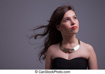 beautiful young woman with hair on wind, looking up, studio shot