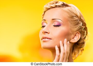 Beautiful young woman with hairdo touching her face with hand