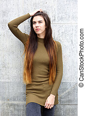 Beautiful young woman with hand in long hair