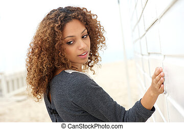 Beautiful young woman with hand on wall and looking over shoulder