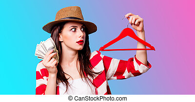 beautiful young woman with hanger and money standing in front of wonderful blue background