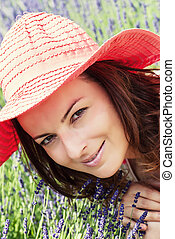 Beautiful young woman with hat in a lavender field