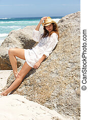 Beautiful young woman with hat leaning against rock on beach