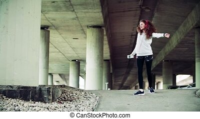 Beautiful young woman with headphones dancing under the bridge in the city.