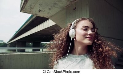 Beautiful young woman with headphones standing under the...
