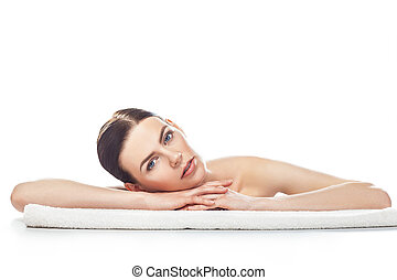 Beautiful young woman with healthy clean skin rest on a towel