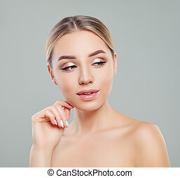 Beautiful young woman with healthy skin looking on copy space on gray background. Facial treatment, skincare and cosmetology concept.