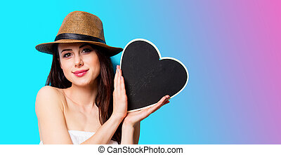 beautiful young woman with heart shaped toy standing in front of wonderful blue background