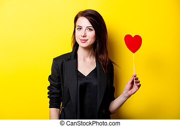 beautiful young woman with heart shaped toy standing in front of wonderful yellow background