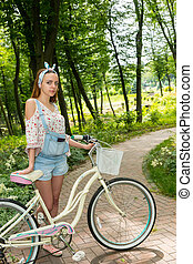 Beautiful young woman with her bicycle standing on a footpath in a park