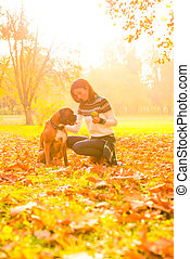 Beautiful young woman with her Dog in the Park
