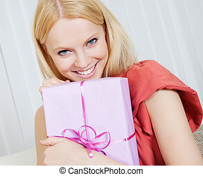 Beautiful young woman with her present