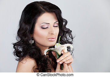 Beautiful young woman with lily flower.