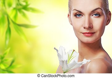 Beautiful young woman with lily flower on abstract background