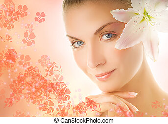 Beautiful young woman with lily flower ove abstract background