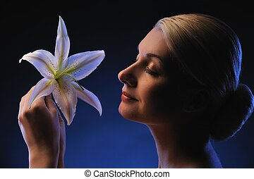 Beautiful young woman with lily flower toned in blue