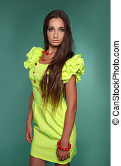 Beautiful young woman with long brown hair. Pretty model poses in fashion style dress at studio.