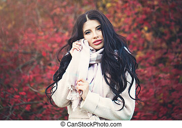 Beautiful young woman with long brunette hair in fall park outdoors. Autumn beauty