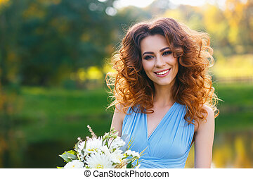 Beautiful young woman with long curly hair