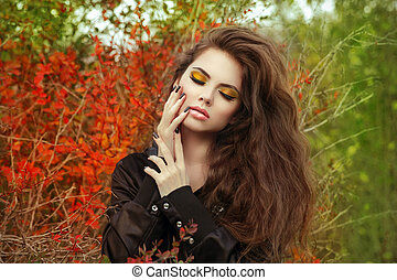 Beautiful young woman with long hair posing outdoors in autumn park