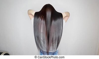A beautiful young woman shows off her long, straight dark hair. Fashion model with sleek gloss hairstyle. The result of keratin hair treatment