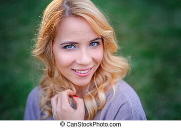beautiful young woman with make-up posing in a summer park