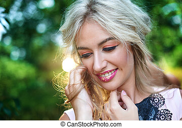 beautiful young woman with make-up posing in the park