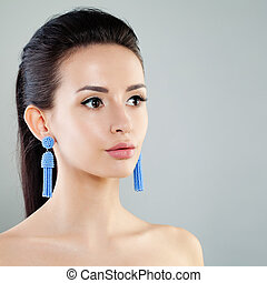 Beautiful Young Woman with Makeup and Blue Earrings