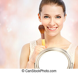 Beautiful young woman with makeup brush