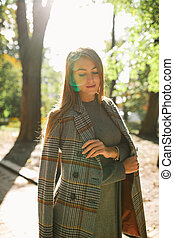 Beautiful young woman with natural makeup wearing warm coat posing with sun flare