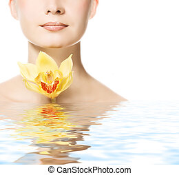 Beautiful young woman with orchid flower reflected in water