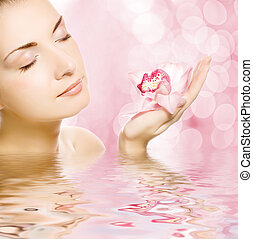 Beautiful young woman with orchid reflected in water