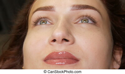 Beautiful young woman with permanent lip make-up and microblading eyebrow tattoo lies with a beauty parlor after the procedure. Close-up girl face.