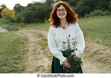 Beautiful young woman with red curly hair and freckles on her face.