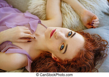 beautiful young woman with red hair lying on the couch