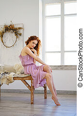 beautiful young woman with red hair sitting in Studio