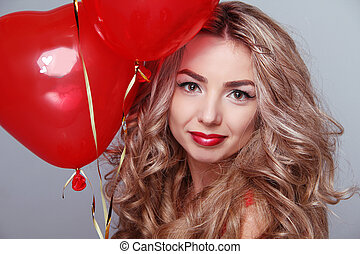 Beautiful young woman with red heart shaped balloons