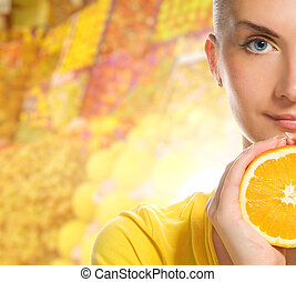 Beautiful young woman with ripe orange