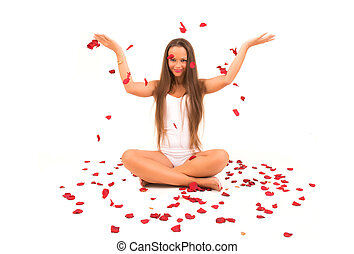 Beautiful young woman with rose petals flying