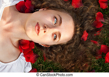 beautiful young woman with rose petals outdoors