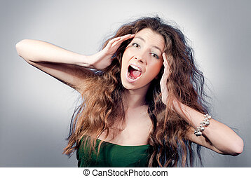 Beautiful young woman with shaggy hairdo screaming